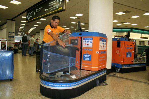 Процесс платной упаковки чемодана в аэропорту