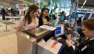 Пассажиры у стоек регистрации в аэропорту